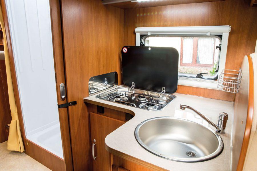 Küchenbereich mit Spülbecken und Gasherd (3-flammig).