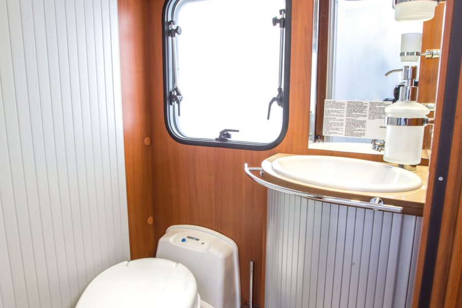 Waschraum mit Waschtisch und drehbarem WC-Sitz.